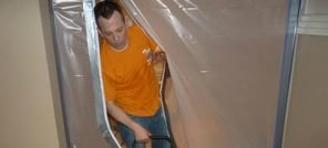 Water Damage Restoration Technician Drying A Living Room