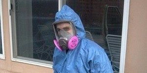 Technician In Fire Damage Removal Gear At A Residential Job Site